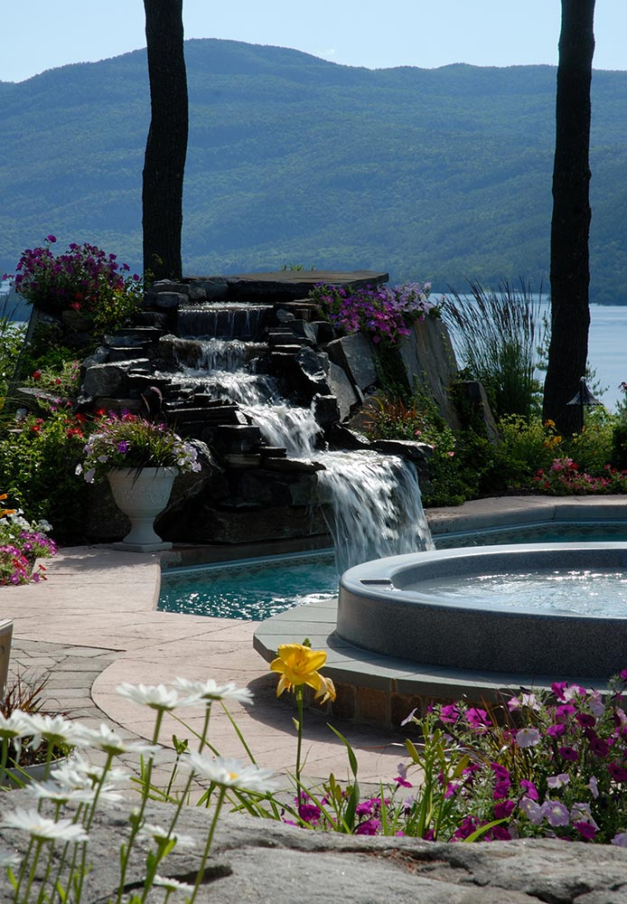 Stone waterfall into pool next to hot tub in Bolton landing